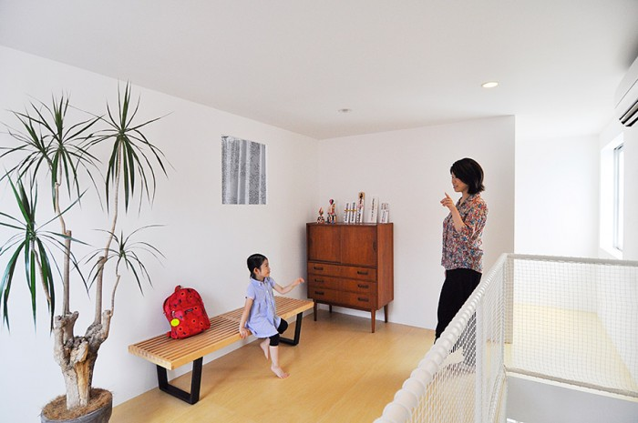 3階寝室前の空間でお話をしている幸希さんと娘さん。娘さんが座っているのはジョージネルソンのプラットフォームベンチ。奥の空間にはバスと洗面、トイレなどの水回りが集められている。