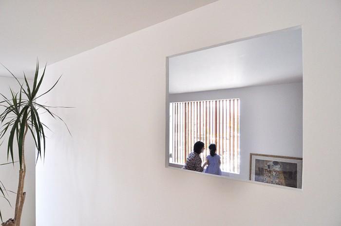 寝室の大きな窓から外を眺める幸希さんと娘さん。寝室との間の壁に設けられた開口がほどよい抜け感をつくり出している。
