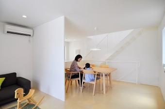 2階のリビングとダイニング。床材には、大きな面で張れて狭さを感じさせないシナベニヤを採用した。