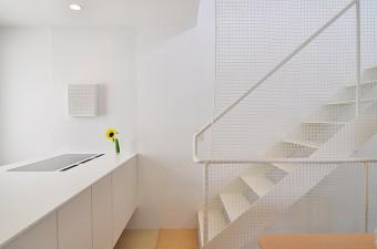 キッチンと3階へと上がる階段。必要最小限に抑えたシンプルなデザイン。