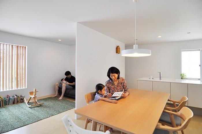 ダイニングとリビングを仕切る薄い壁によって、狭さを感じさせないと同時に奥行き感をつくり出す。テーブルと椅子はマルニ木工の製品で、深澤直人デザインの〈HIROSHIMA〉というシリーズのもの。ランプはflameの凸LAMP。