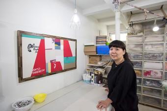 布ナプキン協会理事でもあるユーゴさん。壁のパネルは、Tシャツの布をパッチワークにした作品。http://www.touta.org/