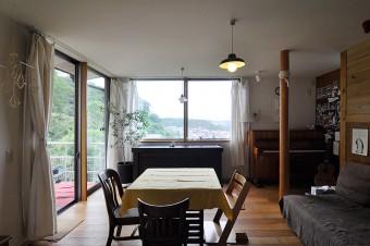 正面の腰高窓の向こうには、街の風景が広がる。左手のデッキにつづく窓からは、裏手の丘の緑が見える。