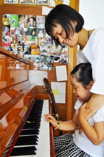 ピアノを弾く蒼衣ちゃんと由香さん。奥の壁には思い出の写真をたくさん貼って。