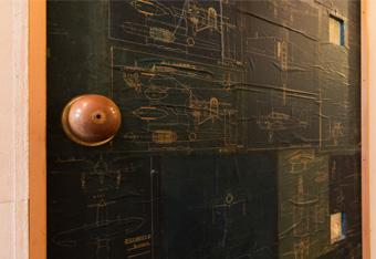 ドアに貼られた航空機の図面は、KINTAさんのお父さんが描いたものだそう。この扉を開けると、工作室になっている。