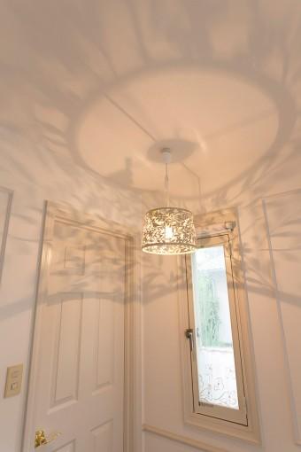 アトリエのシャンデリアはルミネで見つけたもの。白い壁に影が反射する。