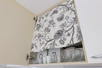 トワル・ド・ジュイの生地を使って、吊り戸棚に取り付けたカーテン。物は隠すのが、美しさのルール。