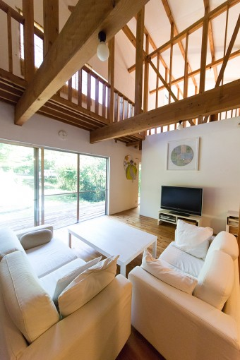 高さのある大きな吹き抜けが気持ちのいいリビング。白い壁にwakaさんの柔らかな色合いの作品が映える。