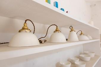 ひとつひとつ形が違う陶器の照明器具。味のある金具やコードが、白い陶器の傘によく似合っている。