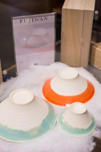 富士山に見立てたロゴが金箔押しされた桐箱。箱を開けると顔を出すのはわたの雲に包まれた富士山型のお猪口とお椀。ひとつひとつの釉薬のかかり方が絶妙。「青富士」と「赤富士」のセットでどうぞ。 Fuji Choco(2個入り・桐箱入り) ¥1575 富士椀 2個 ¥5250  1個 ¥3150