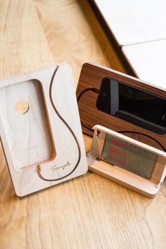 コードの流れまでをデザインしたiPhoneのスタンド。充電しながらWebや動画を楽しめる便利アイテム。交通機関などのICカードがセットできるiPhoneケースにはレーザー刻印で名入れや柄を入れてオリジナリティを。 (左・右奥)Base Station for iPhone5:メープル、ウォールナット ¥4200 (右手前)iPhone Wooden Case for iPhone5 With IC-Pass:メープル ¥7980 ※名入れ、柄入れは別料金