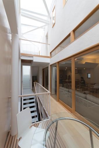 まるで屋外のような2階の階段室。塗り壁の質感が美しい。右手のガラス戸の向こう側がリビング。