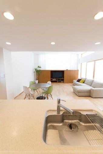 キッチンからリビングダイニングを見る。キッチンは天井が一段低くなっており、落ち着いて料理ができる。
