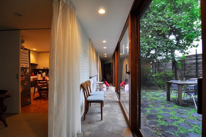 左がキッチン、正面奥の右側に和室。庭とのレベル差がなく、また廊下の石が庭のものと同程度の大きさのため、庭と廊下が連続しているように感じられる。
