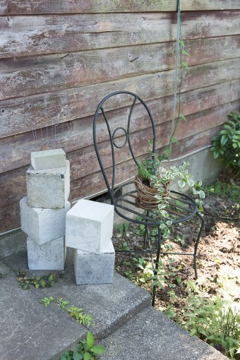 玄関前を自由にディスプレイ。コンクリートブロックやアイアンの椅子など、友人からのもらいものが活躍。