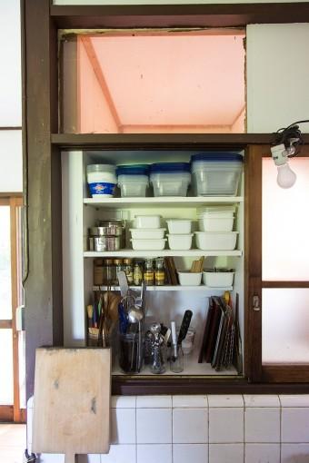 窓しかなかったキッチン前には、収納棚を取り付けて機能的に。裸電球で灯りとり。