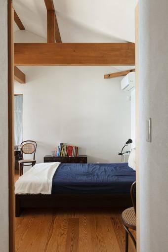 リビングの上に位置する2階の寝室。梁の木組み空間のアクセントになっている。ベッドの位置は、横になった状態で窓から海が見えるように工夫したそう。