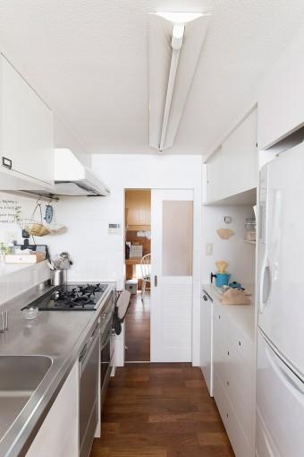 すっきりとして機能的なオープンキッチン。その奥が、仕事も家事もできるユーティリティ。