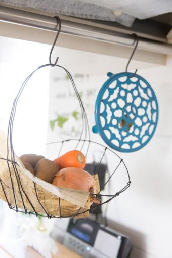 キッチンに吊り下げたワイヤーバスケット。よく使う野菜類はここに常備して、取り出しやすいようにしている。