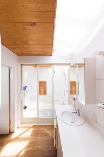 天窓をつけた洗面とバスルーム。手前のトイレにも仕切りがなく、開放的な造り。奥のドアから外のテラスに出られる。