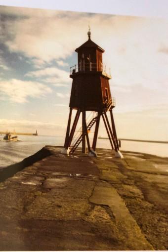 Canvas Printed Shopperのモチーフになった灯台。バブアーが創業したサウスシールズ港の防波堤にある灯台の写真が渋谷店に並ぶ。