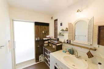 アンティークの鏡などを活かした洗面。木の壁面、ルーバーフェンスなどを取りつけて、味のある雰囲気を出した。