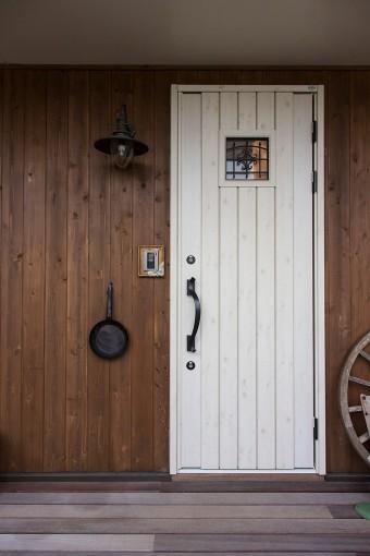 家の顔である玄関には、イギリスのアンティークの照明を。もらったフライパンに名前を書いて、表札代わりに。