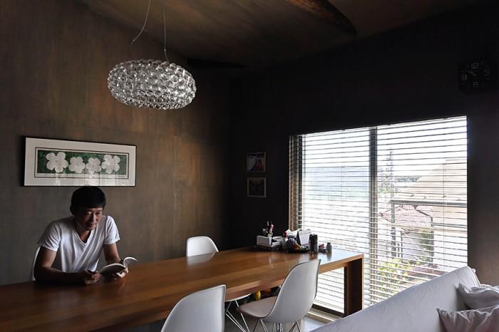 ダイニングスペースで読書中の富永さんの後ろの壁にはウォーホルのシルクスクリーン作品。壁と天井の色は、奥さんが選んだ色とトータルで考えた時に選択した色でもあった。染料の色は黒だが、希釈した上に材に染み込んでこのような色合いに。