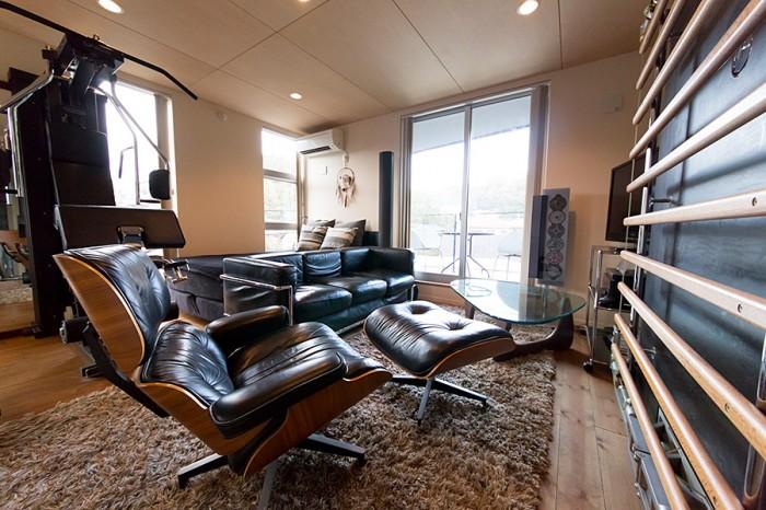 2階のリビングは、黒を基調にした男っぽいインテリア。イームズのラウンジチェア、右側の壁にはテクノジム社の「キネシス」が。