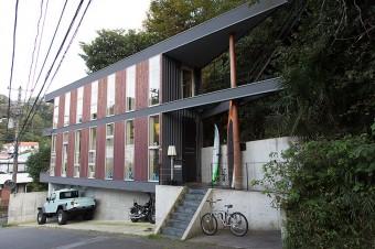 窓と壁がリズミカルに配された外観。家の形が三角なのは、土地を造成せずに自然の傾斜を生かして建てたため。