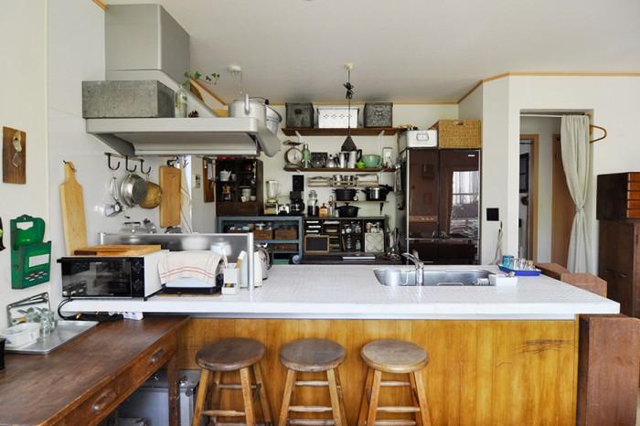 白いタイルや、キッチン台の下の板は自分の手で貼り、古めかしくリメイク。収納も古い棚などを使って完成させた。
