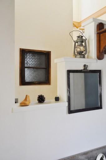トイレの窓は、花柄のガラスを古い窓枠にはめ込んだもの。もとはスロープだった階段横の壁面に段差をつけ、飾り用スペースに。