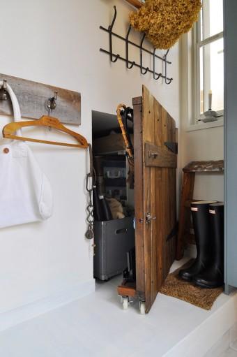 階段下のデッドスペースは、アンティーク風に作った扉をつけて目隠し。