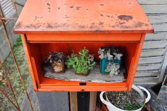 郵便ポストを飾り棚に。左の柵は、骨董市で入手したものを取りつけた。