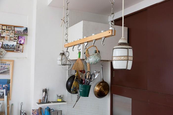 キッチンツールをぶらさげるバーをDIYで制作。横の照明は古道具屋で購入した。