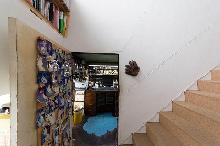 中2階の納戸をアトリエに。床にはベニヤを張り、鮮やかなペンキでペイント。ドアの脇のグローブは、革作家の道に入るきっかけとなったもの。