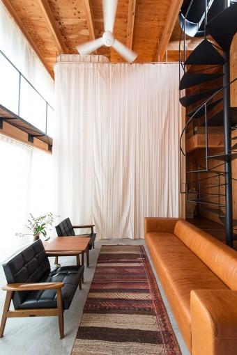シャワーカーテンを閉じた状態。右のソファとラグとテーブルは中目黒の「HIKE」で。左のチェアは「カリモク家具」のもの。