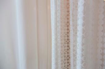 バスルーム、脱衣スペース、2枚のカーテンが重なる部分と、素材が違うものを重ねることで、奥行きのある陰影が生まれる。
