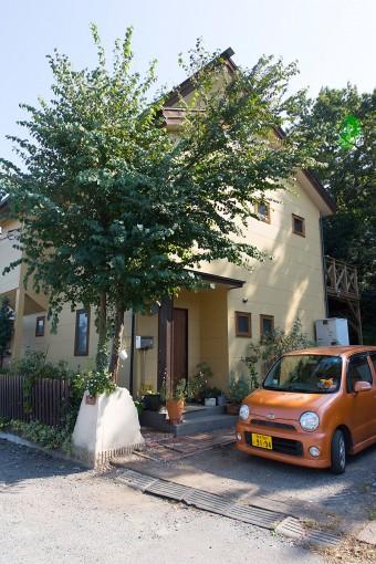 家の前の大きなカツラの木がシンボルツリー。暖色系の外壁が、温かいイメージを与える。
