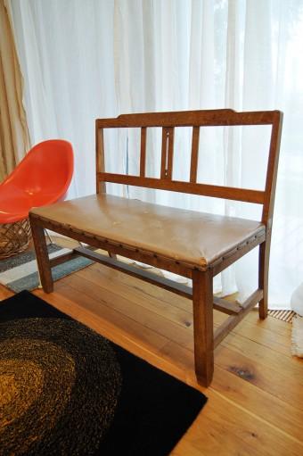 医院で使われていた長椅子はリビングの窓際に。そのお隣にはオレンジ色に塗り替えたシェルチェア。