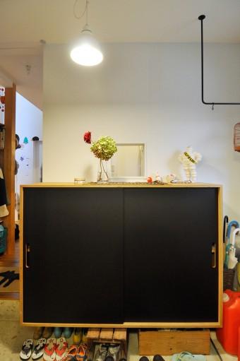 黒い靴箱の向こう側にキッチン。左奥にダイニング。