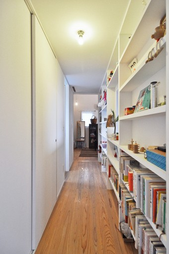 2階の寝室へと向かう廊下には、本や家族で製作した小物などが並べられている。