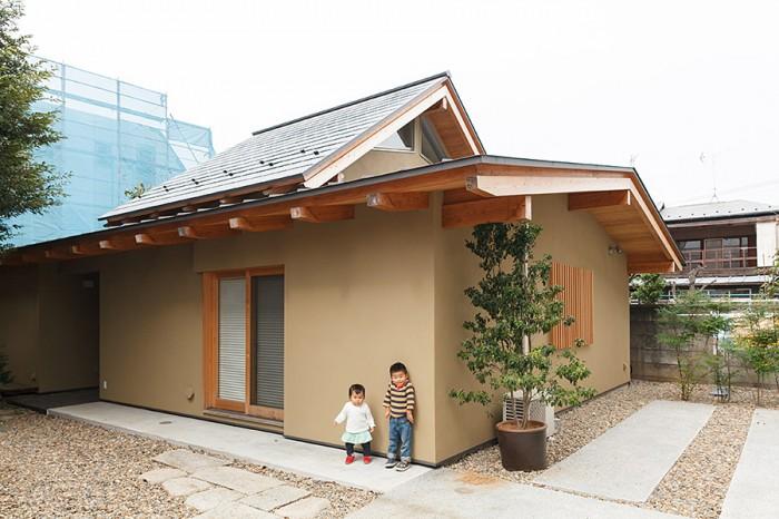和の趣を感じさせる外観。屋根の一段高くなったところにロフトがある。写真右手のスペースがカーポート。庭は子どもたちにとって格好の遊び場でもある。