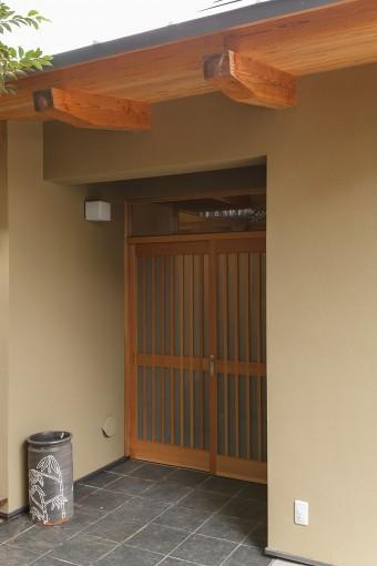 格式を感じさせる玄関。黒いタイルは玄関土間からキッチン、さらに勝手口へと続いている。