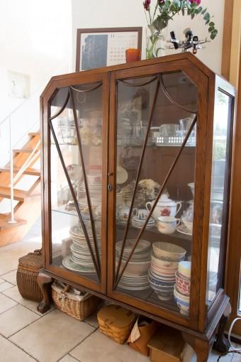 イギリスのアンティークキャビネット。陶器やガラス食器もアンティーク。