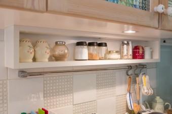 スパイスなどがちょうど収まる棚。キッチンまわりは白のタイルで統一した。