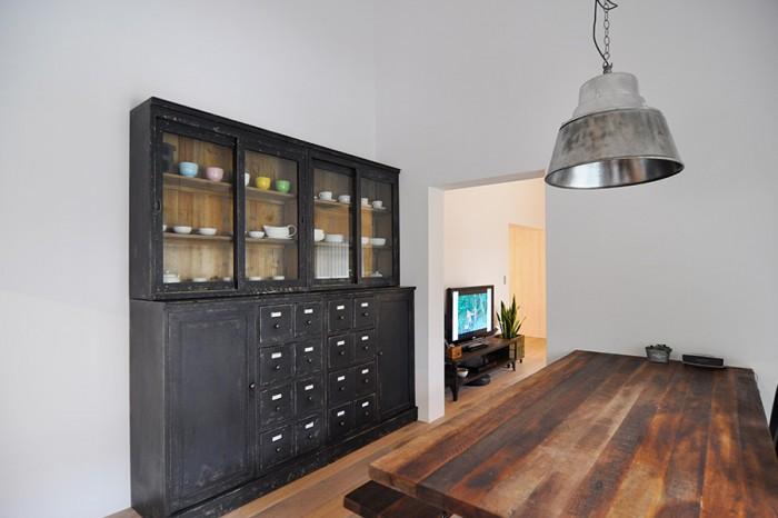 ダイニングに置かれた収納棚とダイニングテーブル。アンティークに見えるがエイジング加工を施された製品。