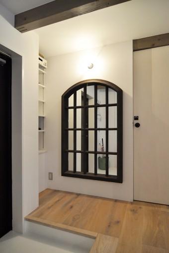 35キロもあるという鏡が玄関の脇に据えられている。スチールフレームの質感が気に入って購入したもの。
