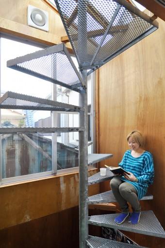 家の奥にある螺旋階段で読書中の比護さん。その日の最も心地いいところで過ごす。