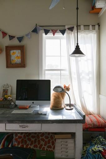 仕事&趣味の部屋のデスクまわり。大きな上げ下げ窓からは、庭が眺められる。